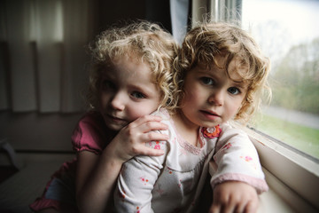 Portrait of sisters leaning on window sill at home