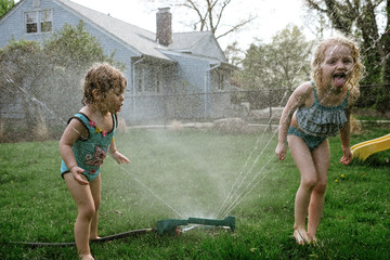 Girls drinking from spraying water at lawn