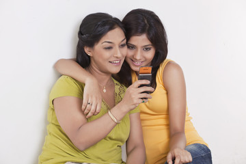 Smiling mother and daughter looking at cell phone