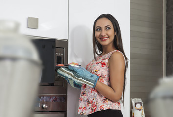 Young woman baking cupcakes in oven