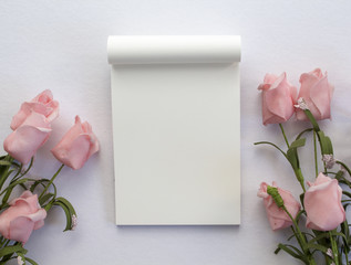 Wedding backdrop with roses and blank white page notepad.