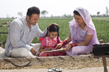 Indian mother and father helping daughter with her homework