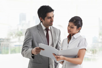 Young businessman looking at female colleague with document in hand