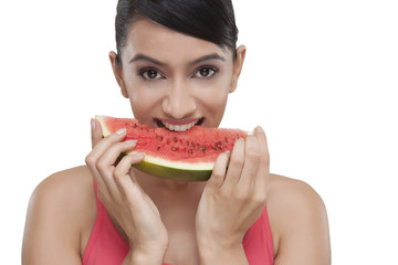 Portrait of beautiful young woman biting slice of watermelon over white background