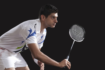 Young male player with racket playing badminton isolated over black background