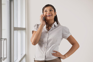 Happy businesswoman speaking on mobile phone