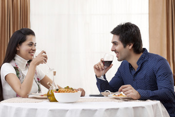 Happy young couple having wine at restaurant