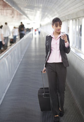 Young businesswoman with luggage reading text message in an airport