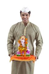 Portrait of a Maharashtrian man holding a Ganesh idol