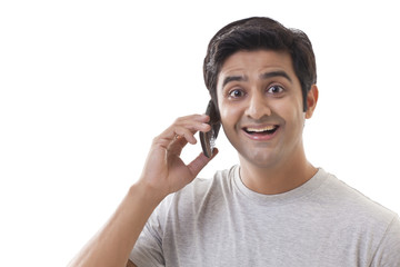 Smiling young man using mobile phone over white background