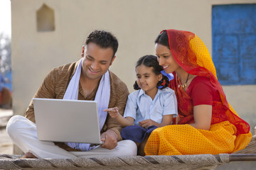 Rural Indian family using laptop while sitting on a cot