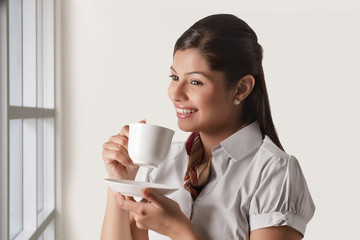 Thoughtful businesswoman having cup of tea for refreshment