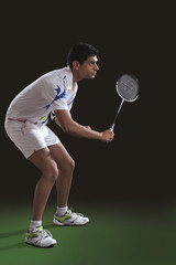 Concentrated young man in sportswear playing badminton over black background