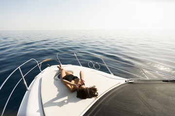 Young attractive woman poses on  luxury yacht floating on sea