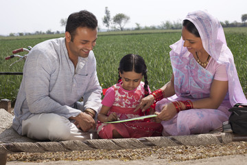 Father and mother assisting daughter with her homework