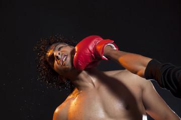 Male boxer striking opponent