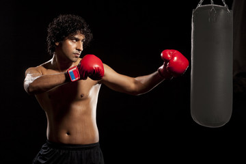 Man working out with a punching bag over black background