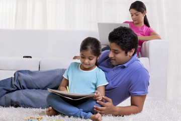 Father assisting daughter while mother working on laptop
