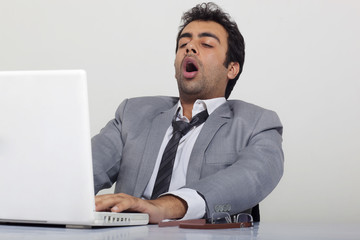 Businessman yawning at work