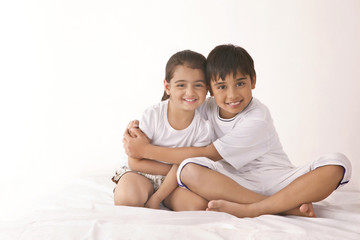 Portrait of happy brother embracing sister in bed