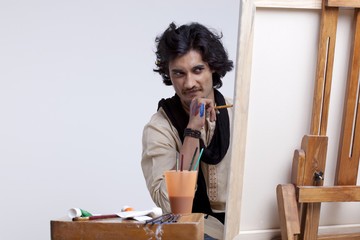 Young male artist looking at painting against colored background