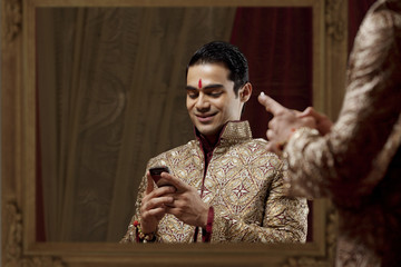 Young bridegroom text messaging in traditional outfit while using mobile phone