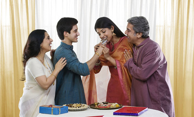 Brother feeding his sister during Rakhi