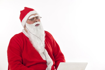 Santa Claus listening to music with eyes closed while using laptop over white background