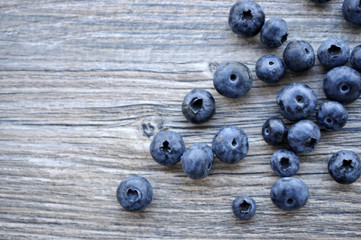 A large bright juicy appetizing blueberry is scattered on a gray board