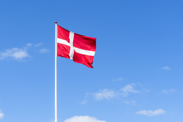 The danish flag in red and white waving in the wind