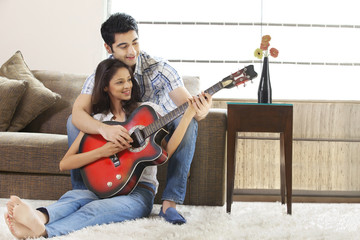 Relaxed young couple playing guitar together at home