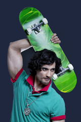 Young man posing with skateboard against black background