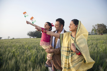 Rural family standing in the field holding Indian flag