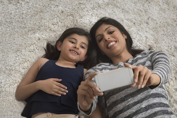 Mother and her little daughter lying on the carpet taking selfie with smartphone