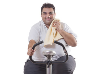 Portrait of a smiling obese man exercising over white background