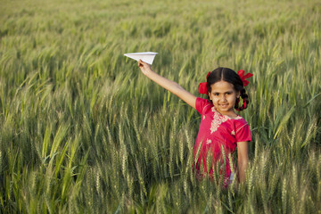 Portrait of little girl playing with a paper aero plane in wheat field
