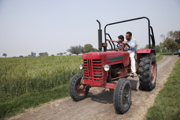 Little boy showing something to father while sitting in tractor
