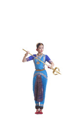 Full length of dancer holding trident while performing Bharatanatyam against white background