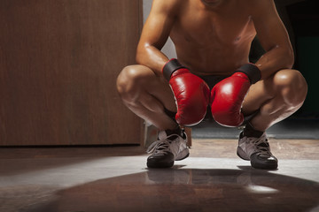 Low section of man wearing boxing gloves crouching in gym