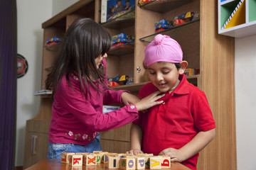 Little boy looking at wooden toy blocks while standing with sister