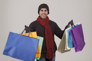 Portrait of young man holding shopping bags