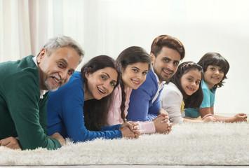 Happy three generation family posing on carpet