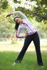 An attractive young woman exercising in park