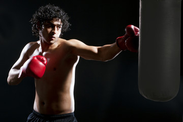 Male boxer hitting heavy bag over black background