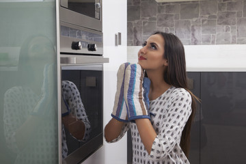 Young woman opening a microwave in the kitchen