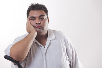 Portrait of a tired obese man with hand on face over white background
