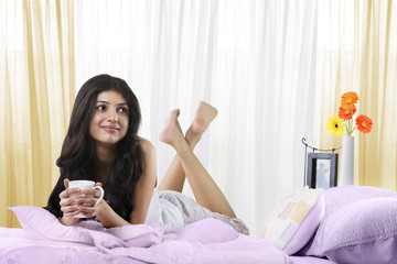 Young girl in bed with a cup of coffee