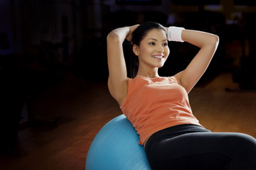 Beautiful young woman doing abdominal exercise on a fitness ball