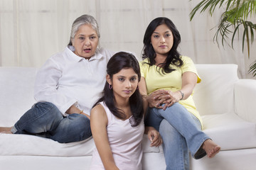 Family with serious expression watching television