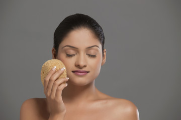 Close-up of young woman using massage sponge over grey background